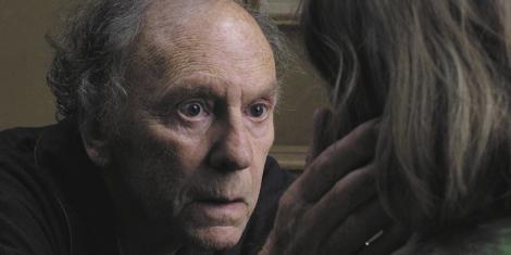 Vi ser rollefiguren Georges, som er en eldre mann med grått, mellomlangt krøllete hår på sidene og baksiden av hodet. Vi ser ham fre brystkassen og opp. Han er til venstre i bildet, og hans høyre hånd hviler på ansiktet til en kvinne med grått, mellomlangt hår, og med bakhodet vendt til kameraet. Mannen ser på henne med store øyne og et intenst blikk, mens munnen er såvidt åpen. Fra høyre side i bildet strømmer dagslys inn og treffer hans isse, og kaster skygger på venstre side av ansiktet hans. I bakgrunnen kan vi skimte en gråbrun vegg.