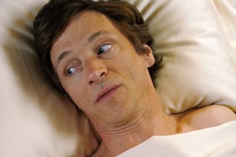 Rollefiguren Mark ligger i sengen. Vi ser ham fra skuldrene og opp. Han har en kremhvit dyne på skuldrene, og puten hodet hans hviler på, er i samme farge. Vi ser ham litt skrått ovenfra,. Han har hodet såvidt snudd skrått ned mot høyre. Øyenbrynene hans er litt hevet, og blikket hans ser til høyre, ut av bildet. Munnen hans er såvidt åpen.