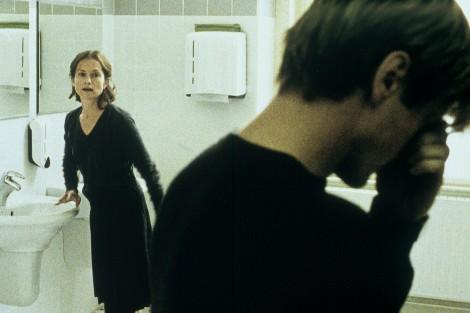 Vi ser en mann og en kvinne i bildet. De befinner seg på et offentlig toalett med lyse fliser på veggene, og man kan se en papirdispenseren til høyre for kvinnen. Vi ser henne fra knærne og opp. Hun har på seg et mørkt skjørt og en mørk, v-utringet genser. Håret hennes er mørkblondt, rekker henne til litt over skuldrene og er samlet bak ørene hennes. Hun lener seg med høyre hånd på en vask og ser mot mannen. Munnen hennes er lukket. Mannen står med ryggen halvveis vendt mot oss. Han har kort, mørkblondt hår, og nakken er såvidt bøyd, og han er helt tett på kameraet , vi ser ham fra litt under skulderen og opp. Med venstre hånd griper han seg til ansiktet, som om han er fortvilet. Vi kan ikke se nasiktsutrykket hans, bare nakken og skyggene på hans høyre kinn og øre.