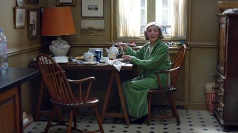 Vi ser skuespillerinnen Emmanuelle Riva som figuren Anne sitte ved et kjøkkenbord, på kortenden, litt til høyre for senter i bildet. Vi ser henne i helfigur, sittende på en stol i mørkt tre med armlener og sprinkelrygg. Hun har på seg en grønn morgenkåpe og ser mot kamera med åpen munn. Med høyre hånd tar hun på en tekanne, med venstre hånd ser hun ut til å holde noe mat. Sollyset treffer toppen av hodet hennes, og rett bak henne er et solfylt vindu med lyse gardiner. På frokostbordet ser vi en tekanne, asjetter og kopper, samt en svær lampe. Bordet står inntil et hjørne, og lampen, med en stor fot av gips som forestiller et fruktfat, har en stor, oransje skjem. På de gråbrune veggene henger forskjellige fotografier av landskap og andre motiver man ikke kan skjelne. Det står en tom kjøkkenstol til venstre for henne, litt til venstre for senter i bildet. Gulvet er hvitt og har mørke, diamantformede detaljer. Til høyre for kvinnen ser vi en kommode, også i mørkt tre. Det er kun dagslys som lyser opp rommet.